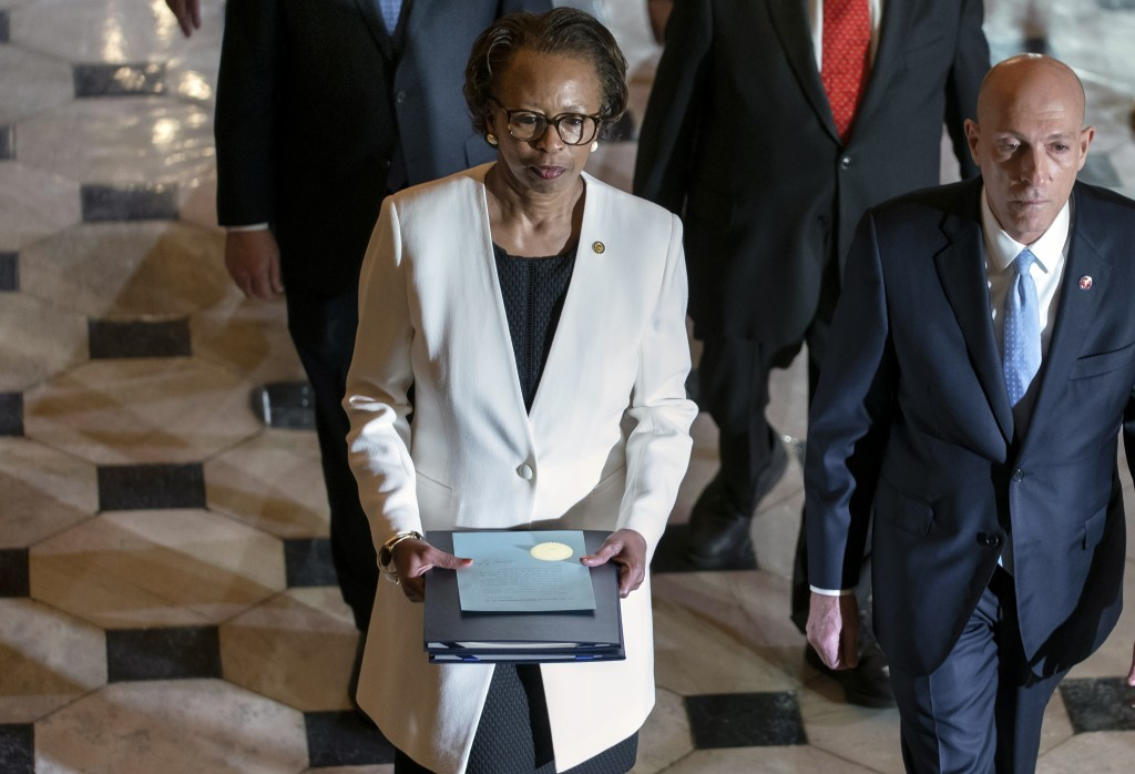 Clerk of the House Cheryl Johnson, center, with House Sergeant at Arms Paul Irving, right, pass through Statuary Hall at the Capitol to deliver the ar...