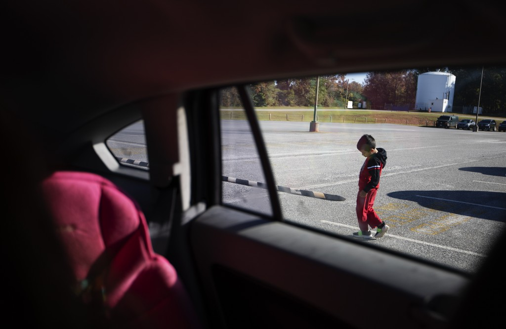A five-year-old boy walks outside his mother's car after they arrive to visit his uncle at the Stewart Detention Center, Sunday, Nov. 10, 2019, in Lum...