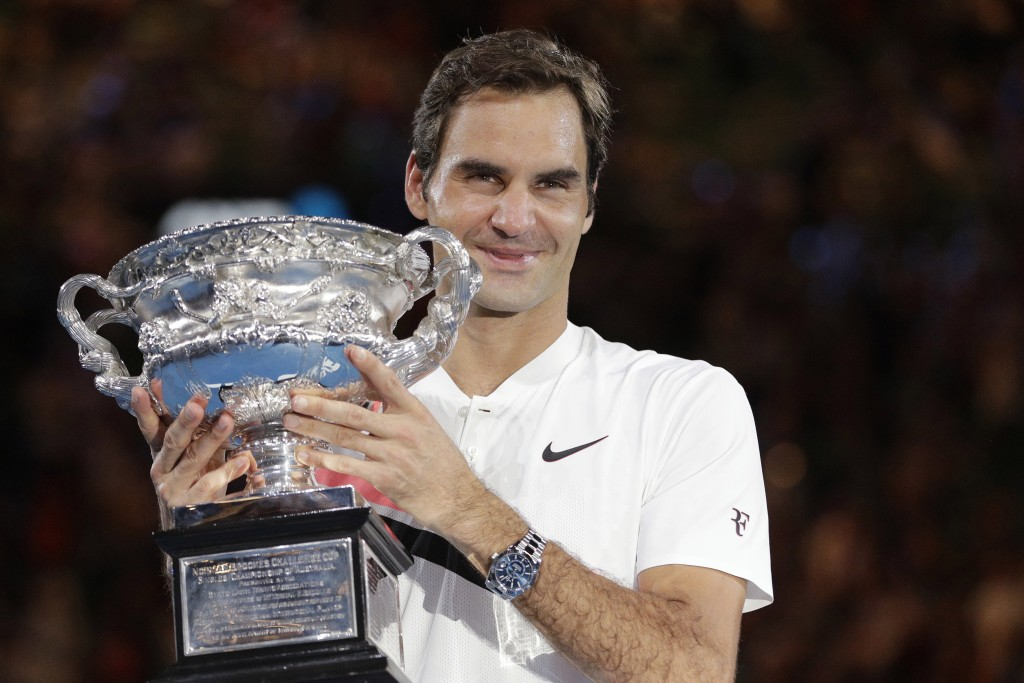 FILE - In this Jan. 28, 2018, file photo, Switzerland's Roger Federer holds his trophy after defeating Croatia's Marin Cilic in the men's singles fina...