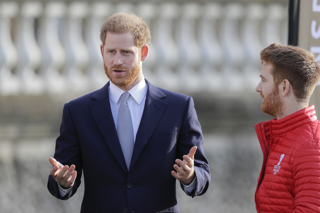 Britain's Prince Harry gestures next to Rugby League World Cup 2021 (RLWC2021) ambassador James Simpson in the gardens at Buckingham Palace in London,...