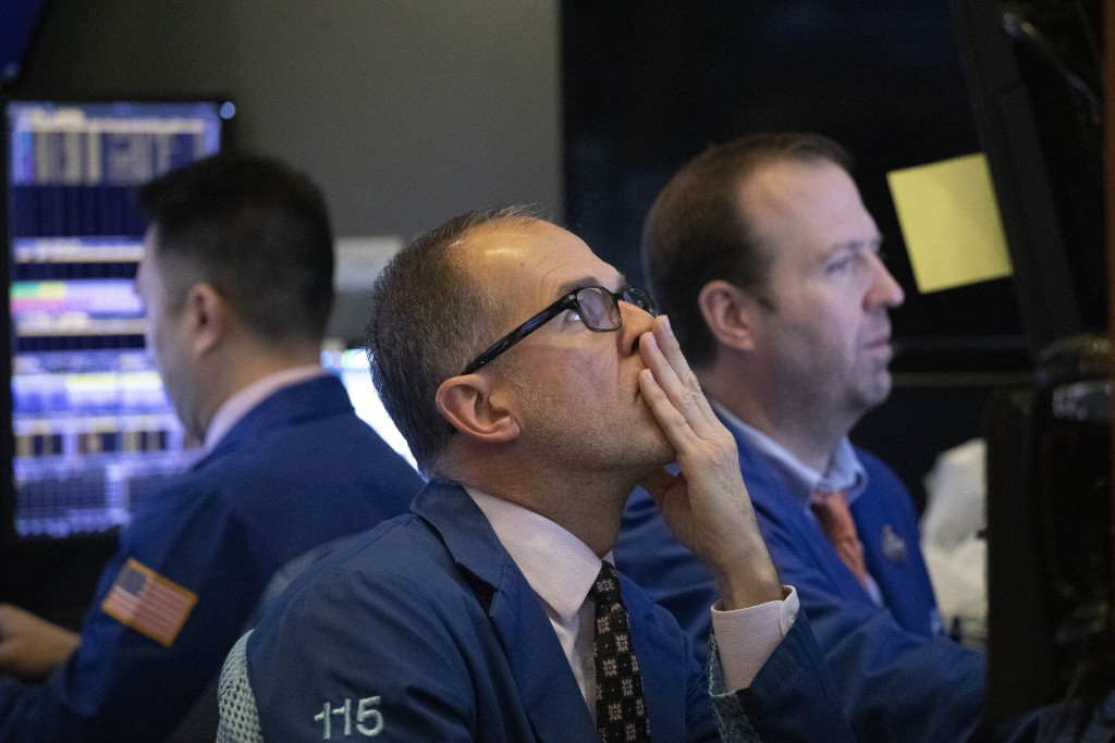 FILE - In this Jan. 2, 2020, file photo traders monitor stock prices at the New York Stock Exchange. Over the next few weeks, companies across the cou...