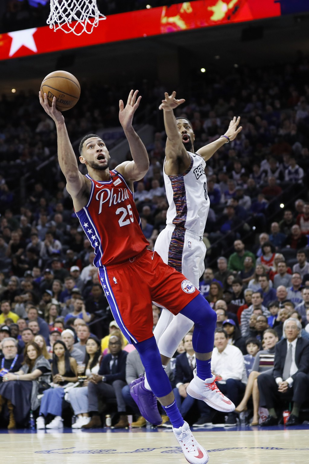Philadelphia 76ers' Ben Simmons, left, goes up for a shot past Brooklyn Nets' Spencer Dinwiddie during the first half of an NBA basketball game, Wedne...