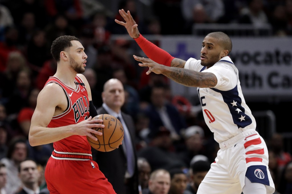 Chicago Bulls guard Zach LaVine, left, looks to pass the ball as Washington Wizards guard Gary Payton II defneds during the first half of an NBA baske...