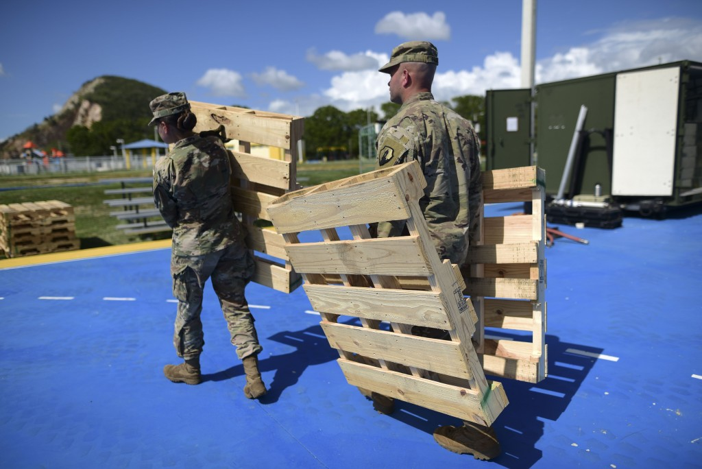 Members of the US army reserve set up portable showers in a tent city for hundreds of people displaced by earthquakes in Guanica, Puerto Rico, Tuesday...