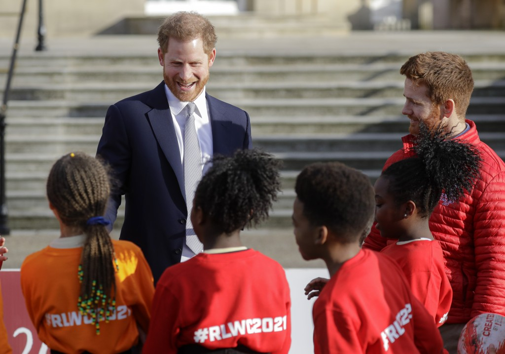 Britain's Prince Harry smiles at schoolchildren in the gardens at Buckingham Palace in London, Thursday, Jan. 16, 2020. Prince Harry, the Duke of Suss...