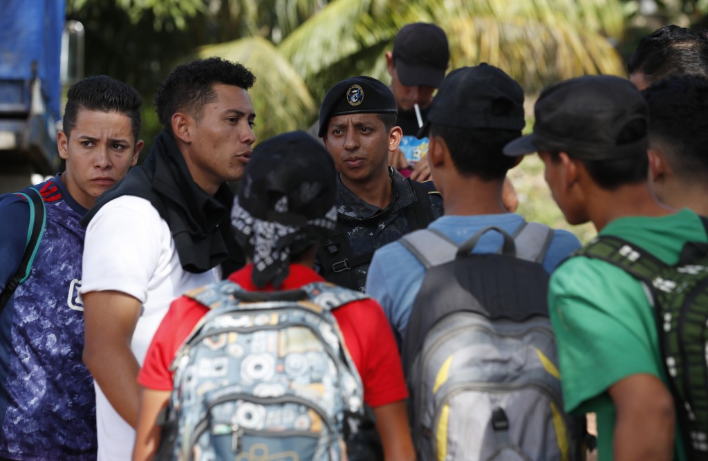 A Guatemalan police officer stops Honduran migrants trying to reach the United States who crossed the Honduran border, in Morales, Guatemala, Wednesda...