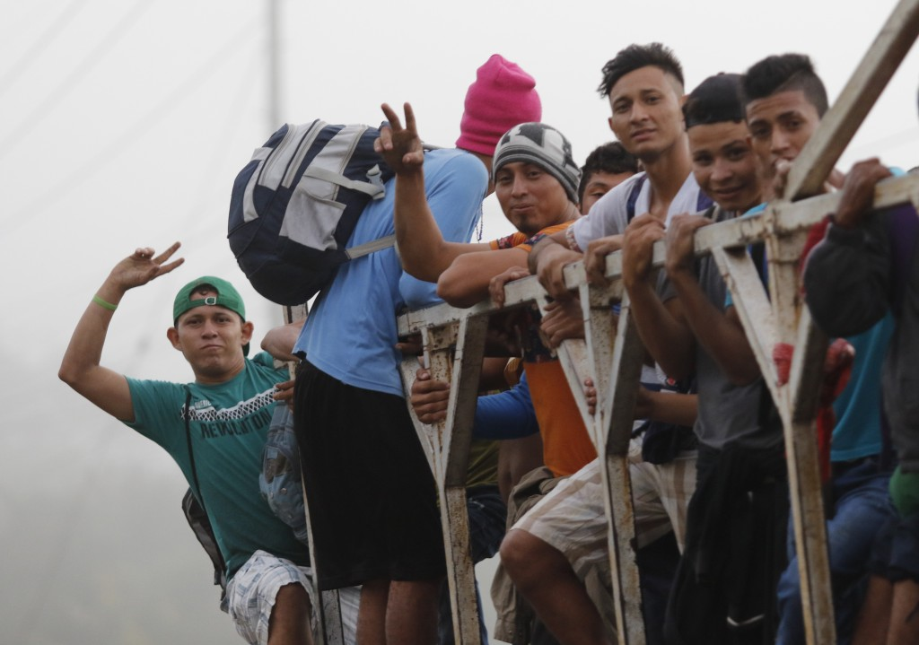 Migrants ride on top of a truck moving along the highway, in hopes of reaching the distant United States, from San Pedro Sula, Honduras, early Wednesd...