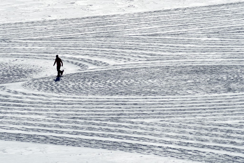 In this photo taken Jan. 7, 2020, British artist Simon Beck uses snowshoes to create a massive geometrical design on a reservoir near Silverthorne, Co...