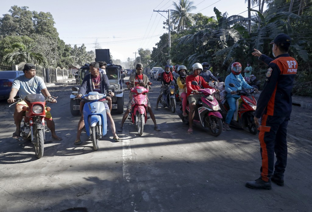 A fireman talks to motorcycle riders at the gates as authorities enforced total evacuation of residents living near Taal volcano in Agoncillo town, Ba...