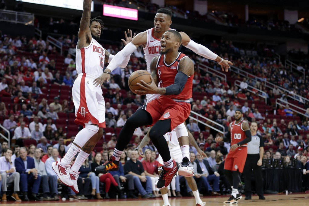 Portland Trail Blazers guard Damian Lillard, middle, puts up a shot in front of Houston Rockets guard Ben McLemore (16) and guard Russell Westbrook, b...