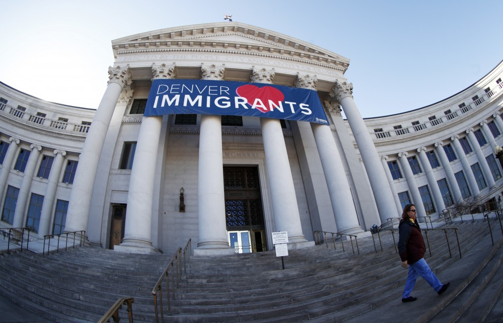 FILE - In this Feb. 26, 2018 file photo, a banner to welcome immigrants is viewed through a fisheye lens over the main entrance to the Denver City and...