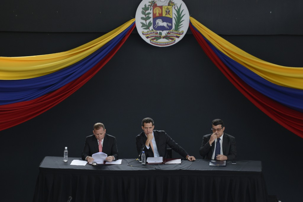 Opposition leader Juan Guaido, center, sits with fellow lawmakers Juan Pablo Guanipa, left, and Carlos Eduardo Berrizbeitia as they hold a session at ...