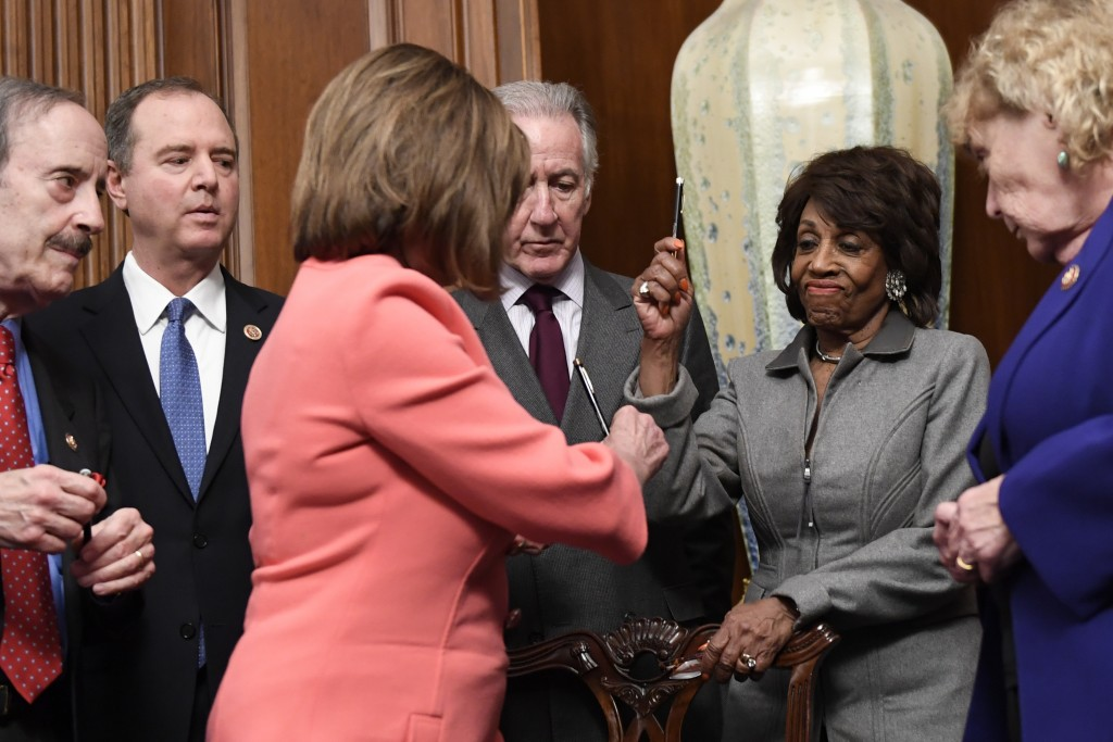 House Financial Services Committee Chairwoman Maxine Waters, D-Calif., second from right, reacts after getting a pen from House Speaker Nancy Pelosi o...