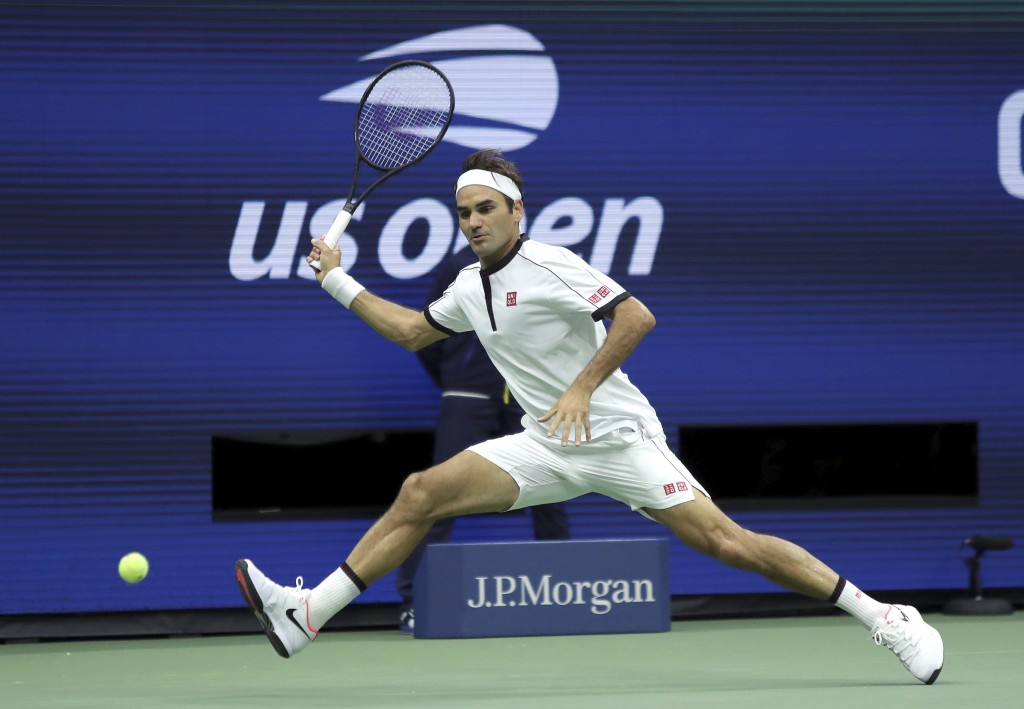 FILE - In this Aug. 28, 2019, file photo, Roger Federer, of Switzerland, returns a shot to Damir Dzumhur, of Bosnia, during the second round of the US...