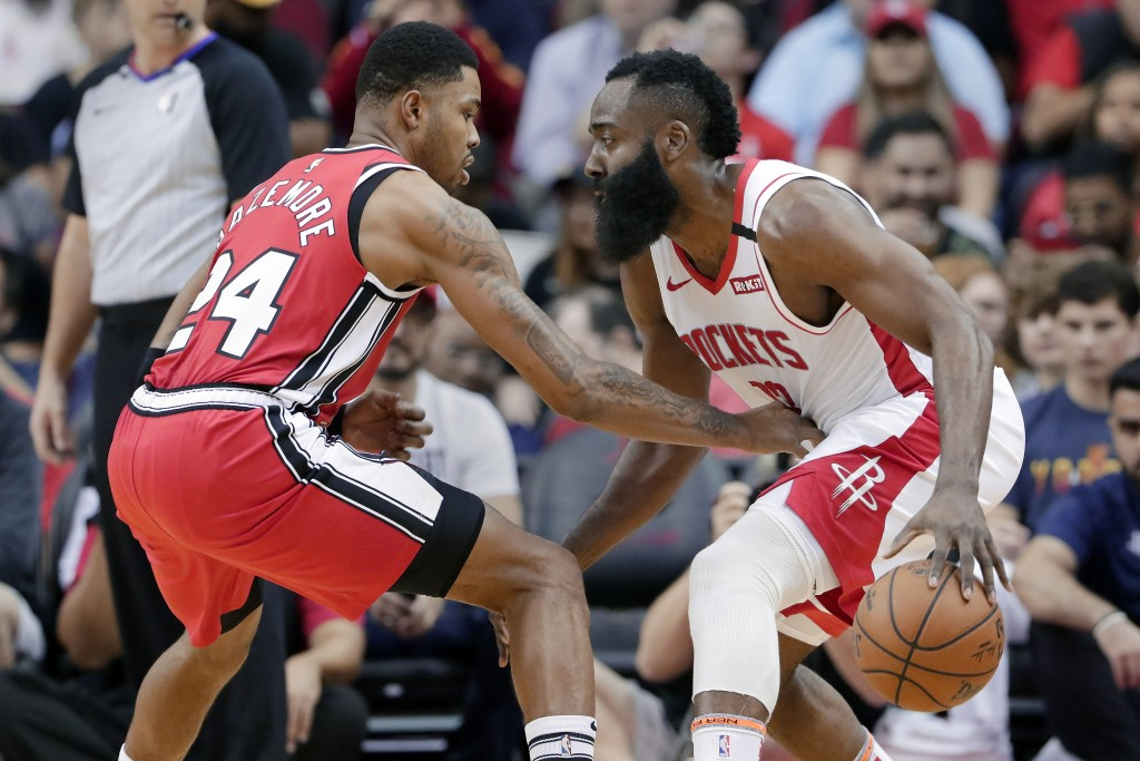 Houston Rockets guard James Harden, right, looks for a way around Portland Trail Blazers guard Kent Bazemore (24) during the first half of an NBA bask...