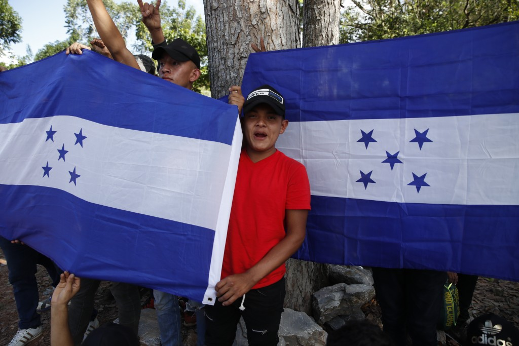 Honduran migrants trying to reach the United States hold up Honduran flags while they are stopped by Guatemalan National Police after crossing the Hon...