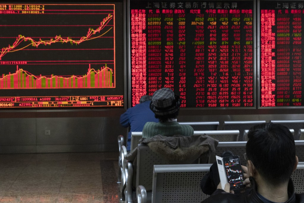 Investors monitor stock prices at a brokerage in Beijing Thursday, Jan. 16, 2020. Share prices are mixed in moderate trading in Asia after the U.S. an...