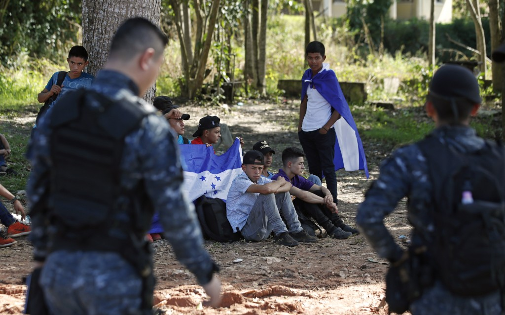 Honduras migrants trying to reach the United States sit with their backpacks and Honduran flags as they are stopped by Guatemalan National Police afte...