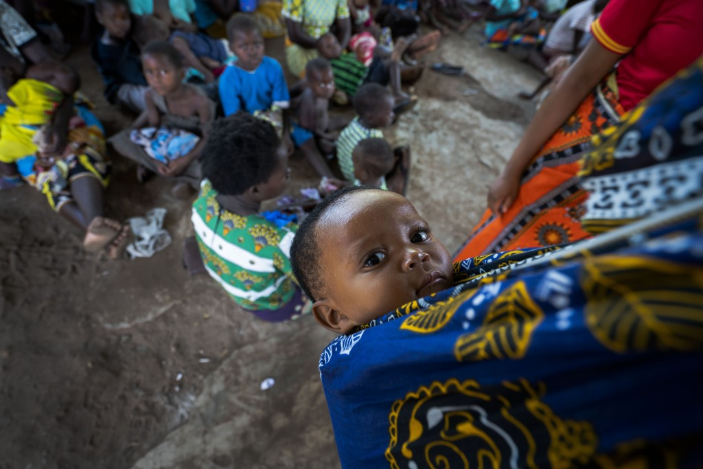 In this photo taken Wednesday, Dec. 11, 2019, residents of the Malawi village of Tomali wait to have their young children become test subjects for the...