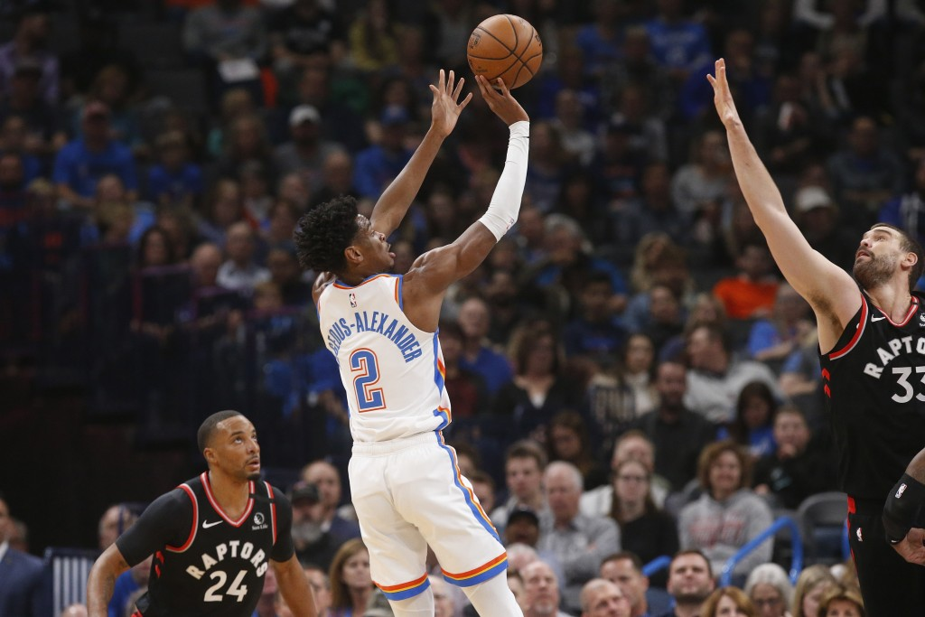Oklahoma City Thunder guard Shai Gilgeous-Alexander (2) shoots between Toronto Raptors' Norman Powell (24) and Marc Gasol (33) during the first half o...