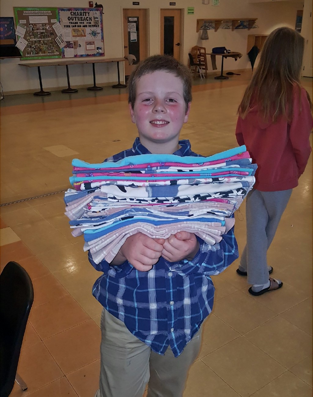 This Jan. 12, 2020 photo provided by Meg Hydock shows Gibson Griffith, 10, holding a stack of fabric crate liners he and others sewed to send to wildl...