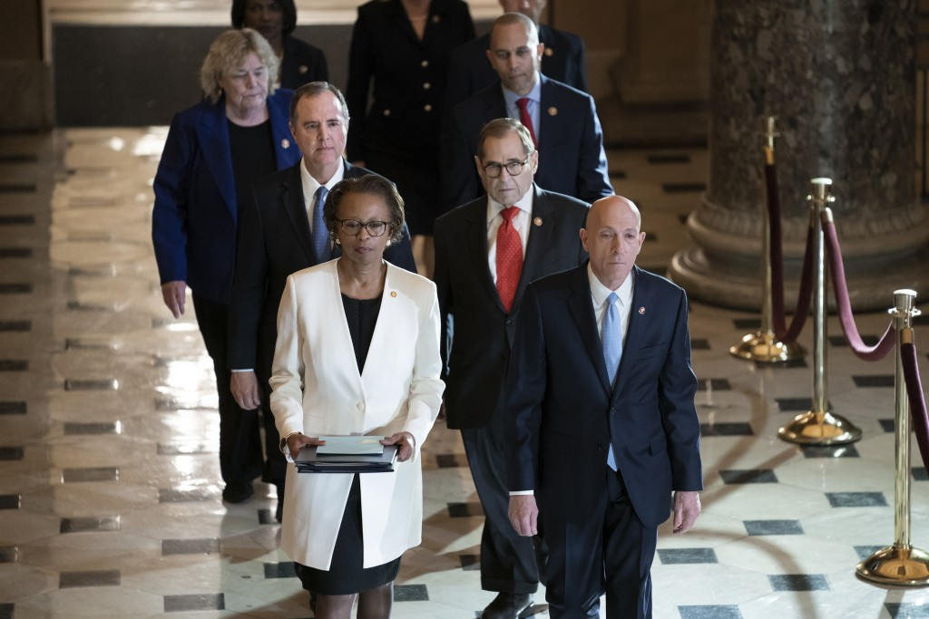 Clerk of the House Cheryl Johnson, left, and House Sergeant at Arms Paul Irving pass through Statuary Hall at the Capitol to deliver the articles of i...