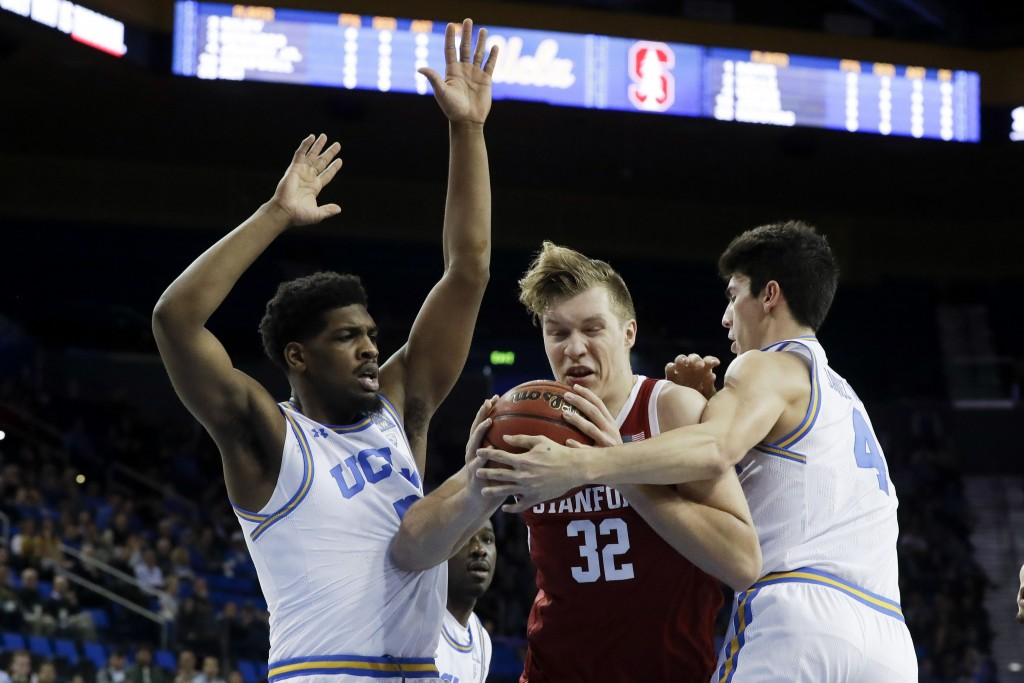 Stanford forward Lukas Kisunas drives the the basket between UCLA forward Cody Riley, left, and guard Jaime Jaquez Jr. during the first half of an NCA...