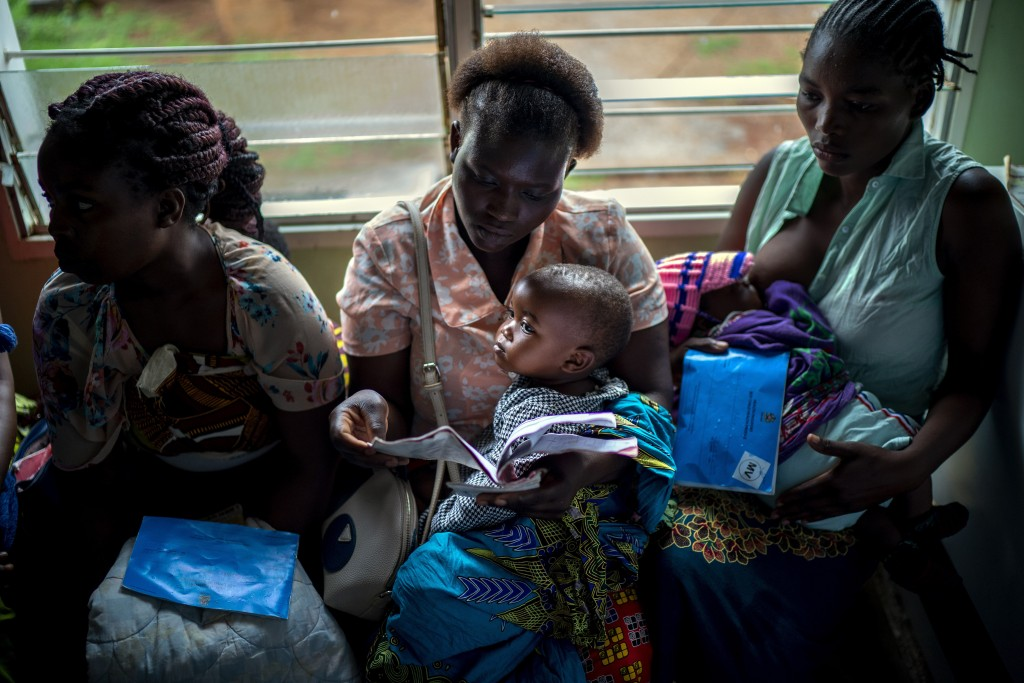 In this photo taken Tuesday, Dec. 10, 2019, residents of the Malawi village of Migowi wait to have their young children become test subjects for the w...