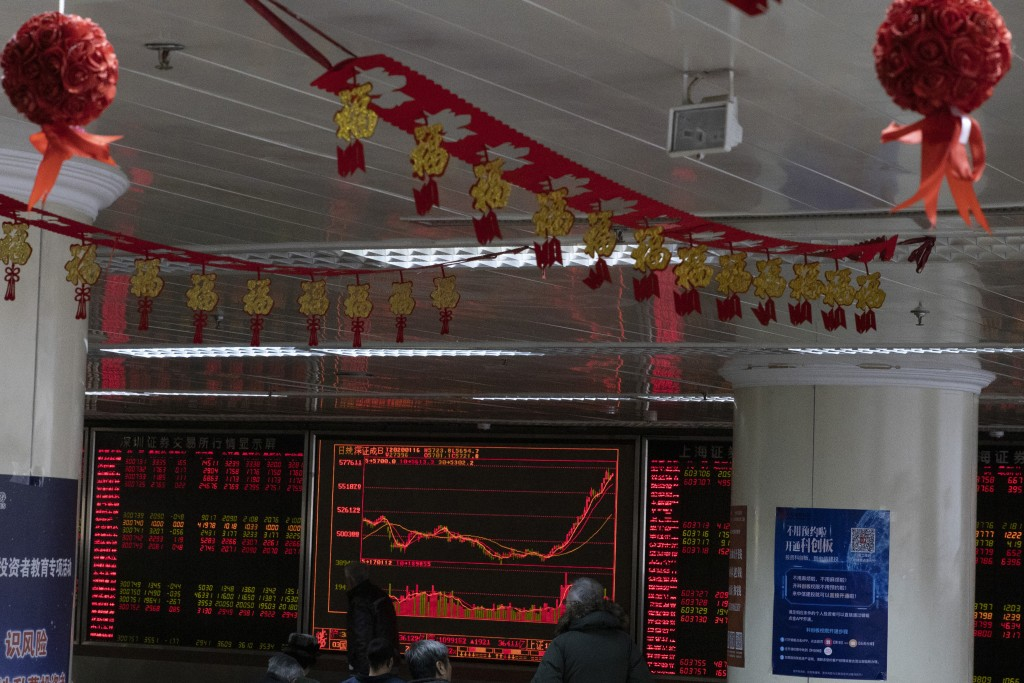 Investors monitor stock prices near Chinese New Year decorations hung up at a brokerage in Beijing Thursday, Jan. 16, 2020. Share prices are mixed in ...