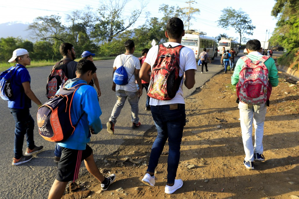 Migrants walk along a highway in hopes of reaching the distant United States, in San Pedro Sula, Honduras, early Wednesday, Jan. 15, 2020. Hundreds of...