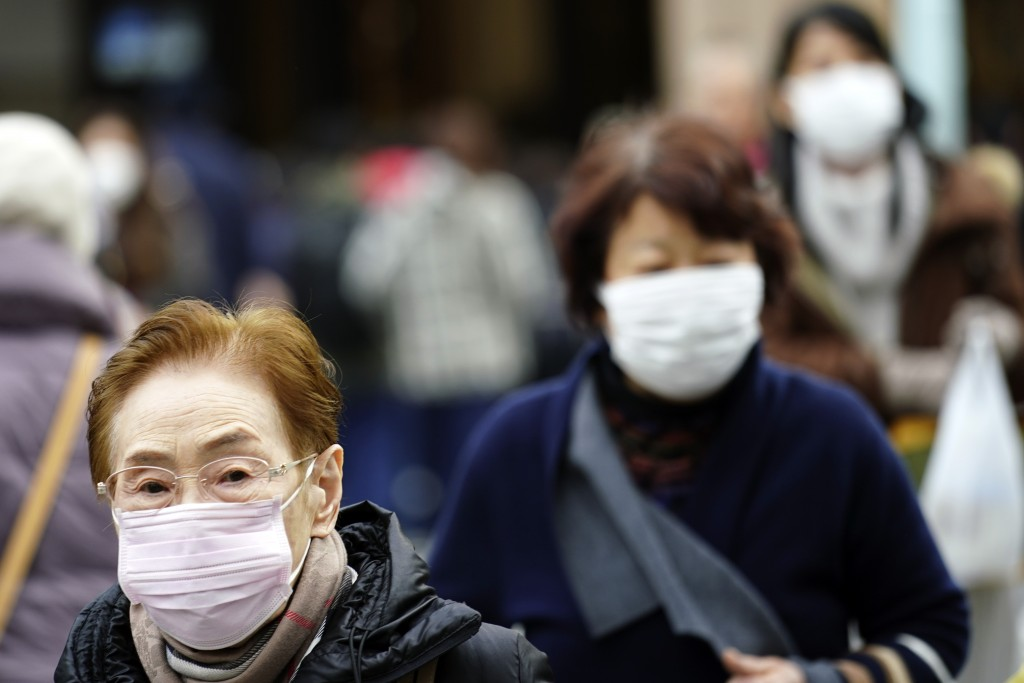 Pedestrians wear protective masks as they walk through a shopping district in Tokyo Thursday, Jan. 16, 2020. Japan's government said Thursday a man tr...