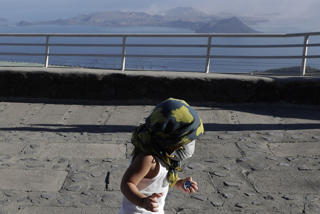 A boy wears a face mask as he plays with Taal volcano in the rear from Tagaytay, Cavite province, southern Philippines on Thursday Jan. 16, 2020. Taal...