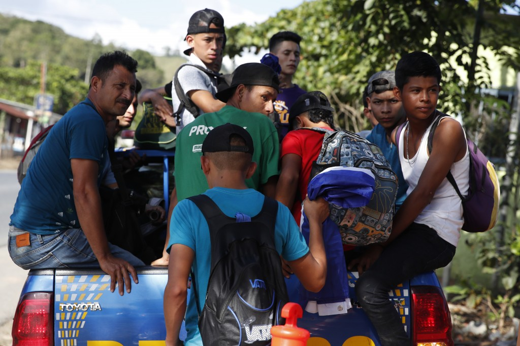 Honduras migrants trying to reach the United States get in the bed of a police pickup truck as they are directed back to Honduran border, in Morales, ...