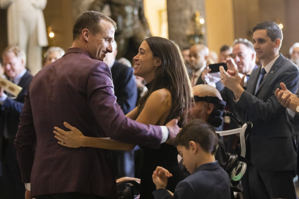 Saints quarterback Drew Brees congratulates Steve Gleason and his wife Michel Gleason, during a Congressional leadership and other members of Congress...