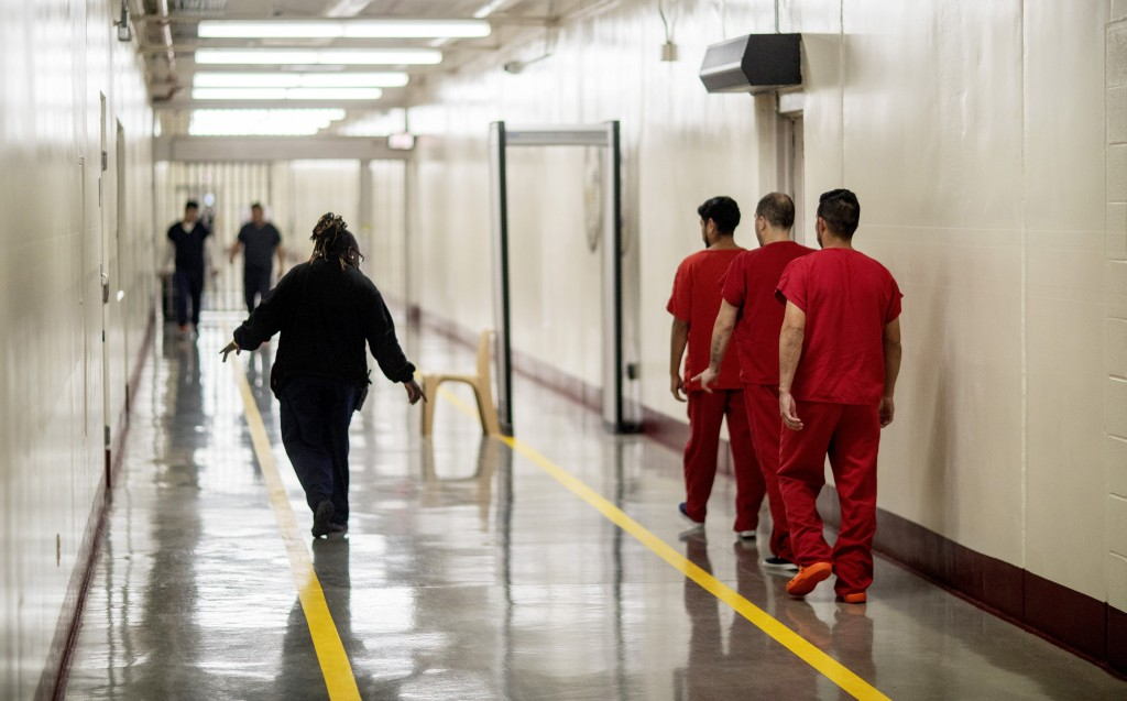 Detainees walk through the halls at the Stewart Detention Center, Friday, Nov. 15, 2019, in Lumpkin, Ga. Immigrants at Stewart are caught in a larger ...