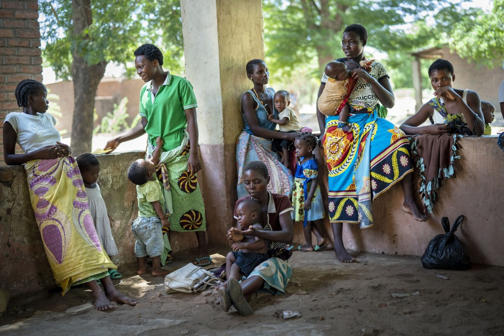 In this photo taken Wednesday Dec. 11, 2019, residents of the Malawi village of Tomali wait to have their young children become test subjects for the ...