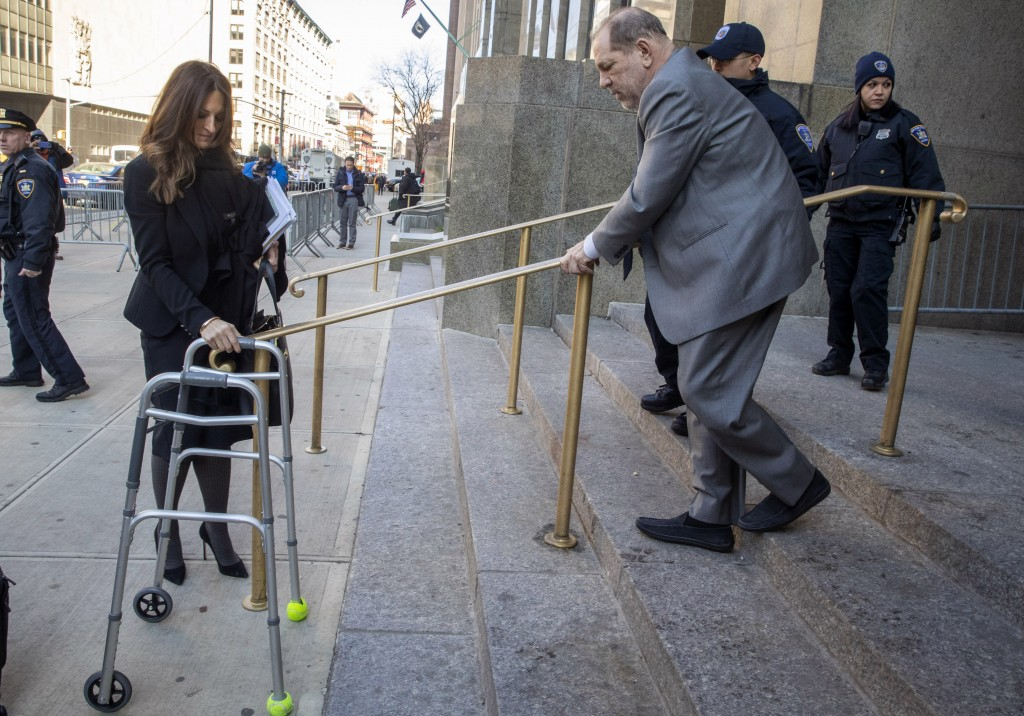 Harvey Weinstein's lead attorney Donna Rotunno, left, holds his walker at the bottom of a staircase as he leaves court for the day during jury selecti...