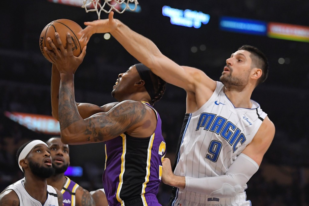 Los Angeles Lakers center Dwight Howard, center, shoots as Orlando Magic center Nikola Vucevic defends during the first half of an NBA basketball game...