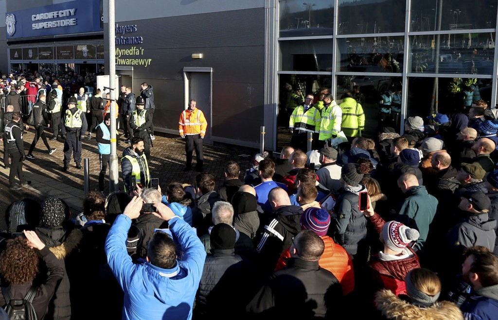 FILE - In this file photo dated Sunday Jan. 12, 2020, soccer fans crowd outside the Cardiff City soccer stadium ahead of the English Championship matc...