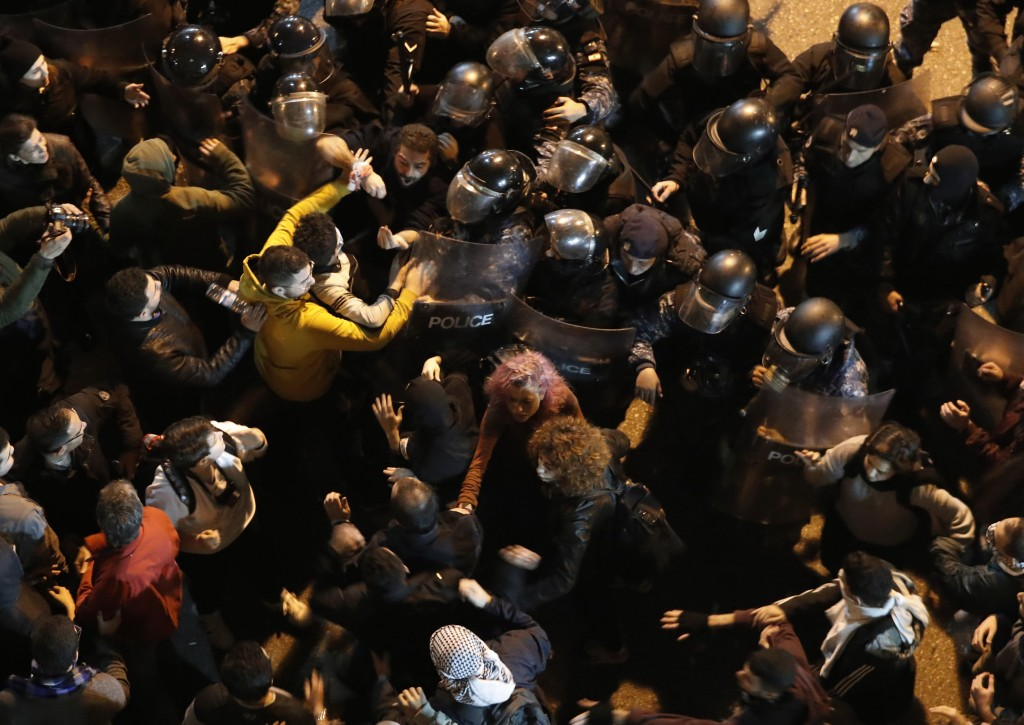 Riot police scuffle with an anti-government protesters who are protesting outside a police headquarters demanding the release of those taken into cust...