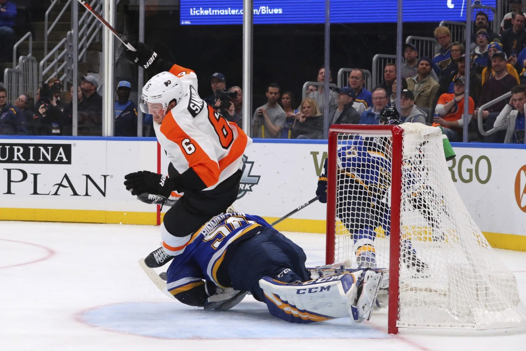 Philadelphia Flyers defenseman Travis Sanheim (6) trips over St. Louis Blues goalie Jordan Binnington (50) during the third period of an NHL hockey ga...