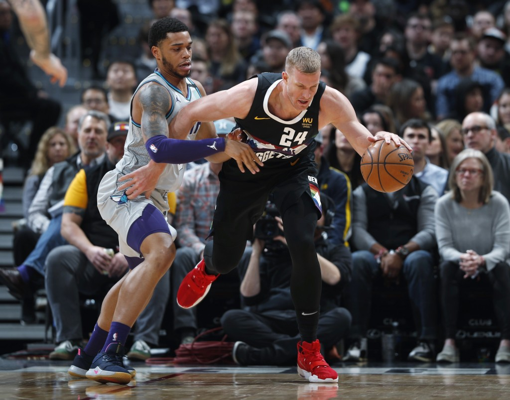 Denver Nuggets forward Mason Plumlee, right, scoops up a loose ball as Charlotte Hornets forward Miles Bridges defends during the first half of an NBA...
