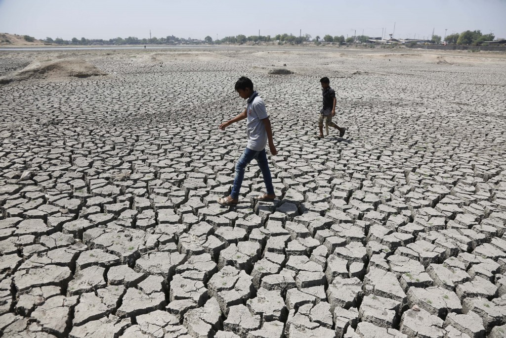 FILE - In this May 14, 2016, file photo, boys on their way to play cricket walk through a dried patch of Chandola Lake in Ahmadabad, India. The decade...