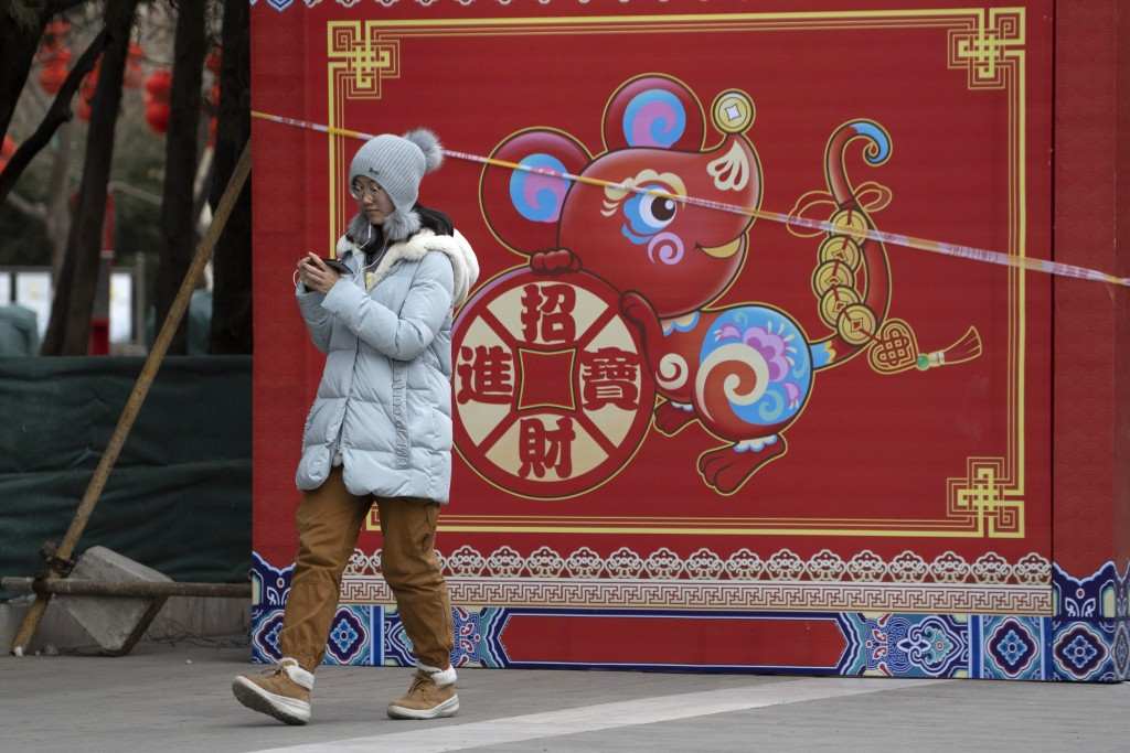 "A woman walks a depiction of a Rat with the words ""Bring in wealth and treasures"" ahead of the Chinese Lunar New Year Year of the Rat celebrations in ..."