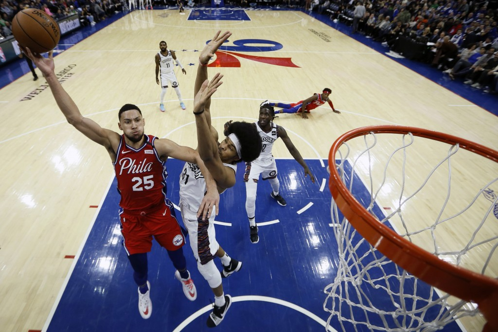 Philadelphia 76ers' Ben Simmons, left, goes up for a shot against Brooklyn Nets' Jarrett Allen during the second half of an NBA basketball game, Wedne...