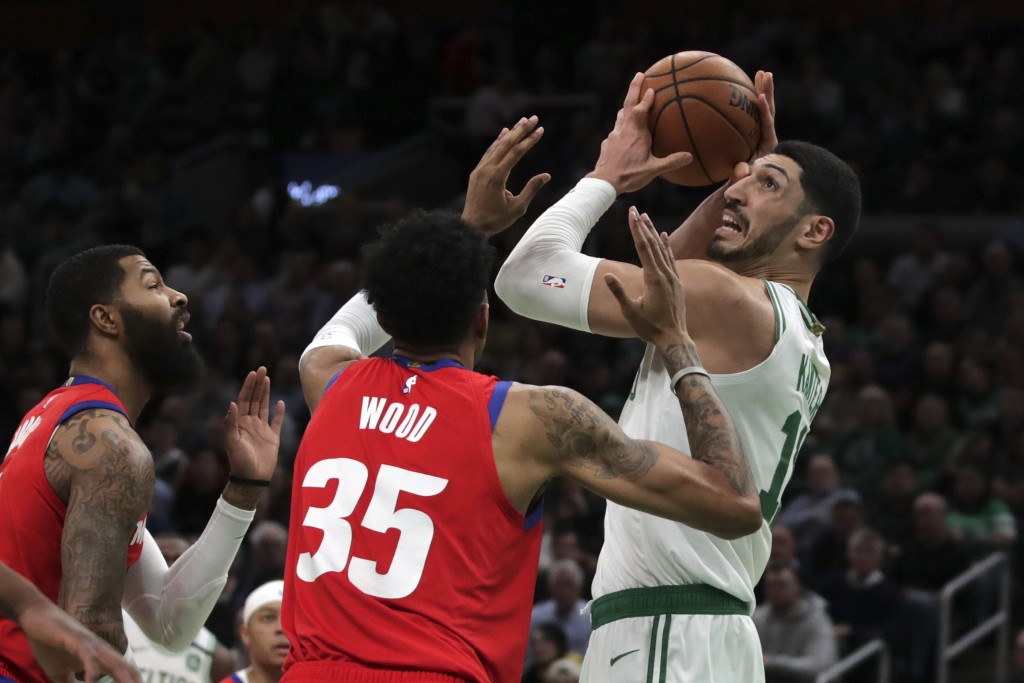 Boston Celtics center Enes Kanter, right, is pressured by Detroit Pistons forwards Christian Wood (35) and Markieff Morris, left, during the first hal...