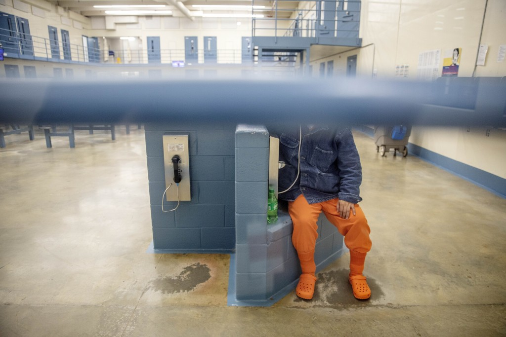 A detainee talks on the phone in his pod at the Stewart Detention Center, Friday, Nov. 15, 2019, in Lumpkin, Ga. It's difficult for detained immigrant...