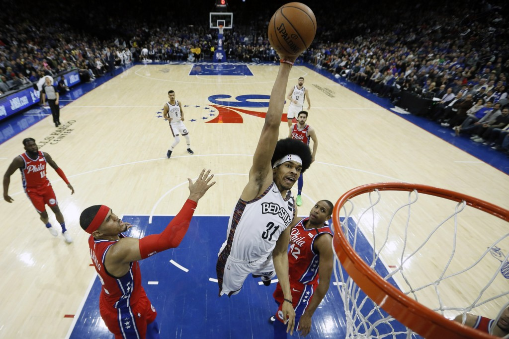 Brooklyn Nets' Jarrett Allen, center, goes up for a dunk between Philadelphia 76ers' Tobias Harris, left, and Al Horford during the first half of an N...