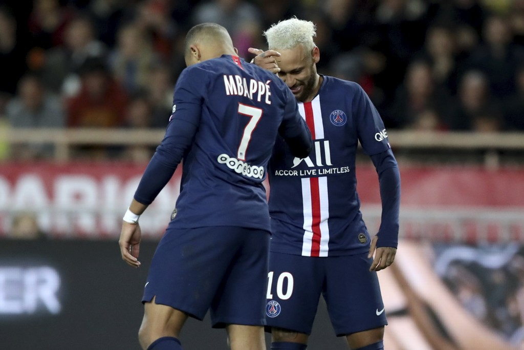 PSG's Neymar, right, celebrates with PSG's Kylian Mbappe after scoring his side's second goal during the French League One soccer match between Monaco...