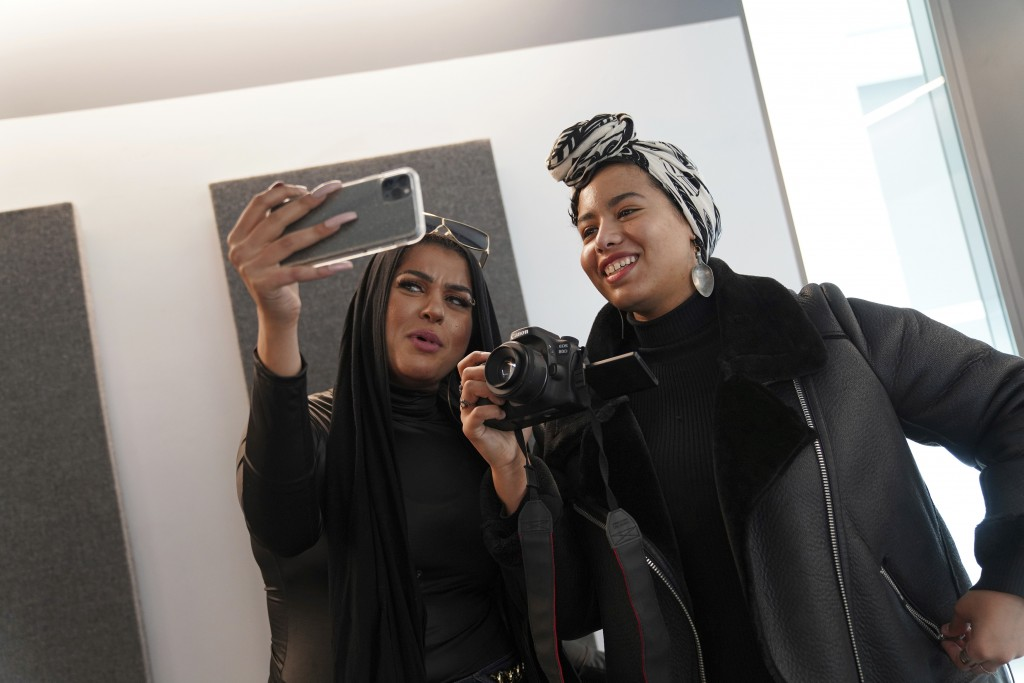 In this Dec. 19, 2019, photo, Amani Al-Khatahtbeh, left, films a video with Maryam Saad after recording a podcast pilot at Spotify's headquarters in N...